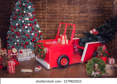 A red Christmas wooden car decorated with branches of spruce and New Year's balls stands at the holiday tree with gifts! Warm lights and bokeh