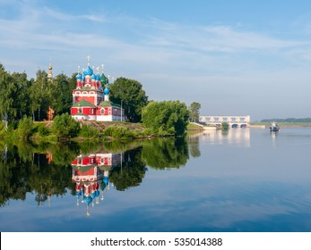 red church with blue domes from Uglich town on the shore surrounded by green trees, view from Volga river at sunny summer day