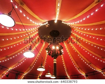 red circus tent interior with hanging lights