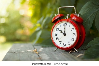 Red classic alarm clock in the garden. Save time, daylight saving concept, web banner with copy space.