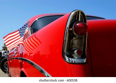 A red classic car with American flag.