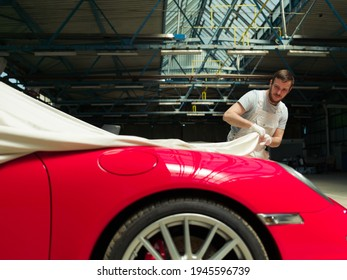 Red classic car  unveiling in the garage