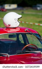 red classic car waiting at the pit for the great race with white helmet resting on the car roof