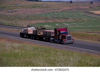 A Red Classic Peterbilt Semi-Truck pulling loaded double flat-bed trailers down an Oregon Highway.  June 20th, 2017 Rural Oregon, USA