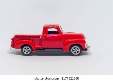 A red classic toy car on a white background