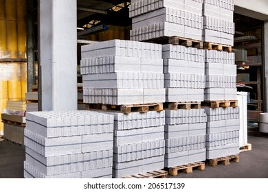 Red clay building bricks stacked on pallets still wrapped in their plastic for delivery at a warehouse, factory or construction site