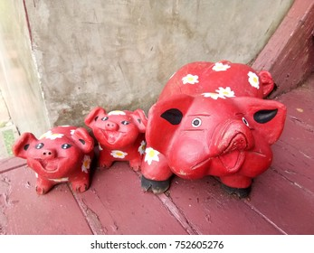 The Red Clay Pigs On the Wooden Floor
