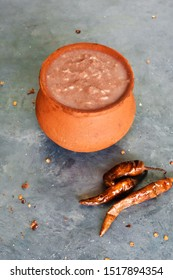 Red clay pot filled with ragi porridge with side dish