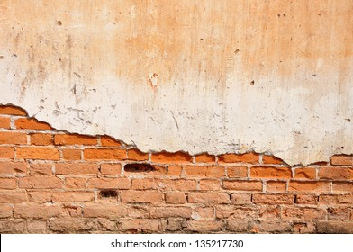 Red clay stained on the white exposed brick concrete wall.