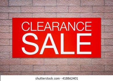 Red clearance sale billboard on brick wall