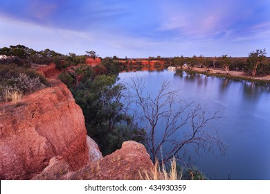 Red cliffs of Murray river on the border between Victoria and New South Wales states of Australia. Elevated red bank of the river overlooks river bend with cruise ship at sunset.