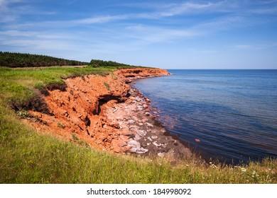 Red cliffs of Prince Edward Island Atlantic coast in Green Gables Shore, PEI, Canada.