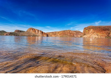The red cliffs surrounding Canyon Lake, reflected in the calm waters on a sunny Winter afternoon