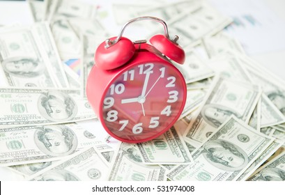 red clock on dollars background ,clock on dollars state, A clock shows the time over American Dollars Bills, time is money business concept with banknotes crown