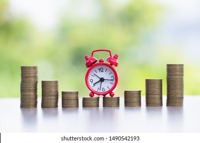 A red clock on a pile of coins.Red alarm clock Put on the coin ladder Ideas to save money, investment, business growth ideas, use the right time to invest.The idea of using time to be worth the money.