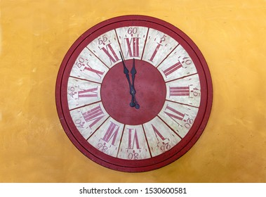 The red clock with Roman numerals shows for five minutes twelve hours. The midnight on tower clock on yellow facade.