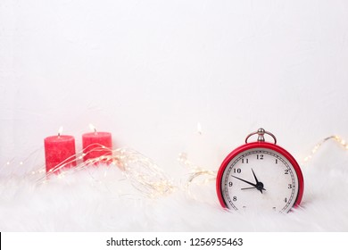 Red clock - symbol of  New Year and birning candles  on white fur background. Winter holidays concept. Time concept. Top view. Copy space.