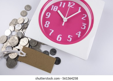 Red clock,coins,green plant and bookmark for time management conceptual text.