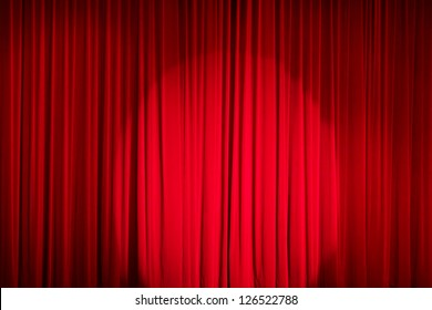 Red closed curtain with a light spot in a theater