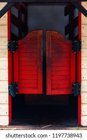 Red closed Western Saloon doors on a white wooden wall on a bright sunny day