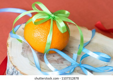 red cloth background on which an orange with a ribbon, a stump on which an orange