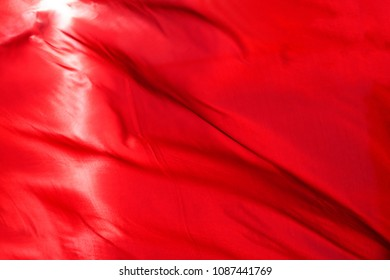 Red cloth or silk flag waving at wind. Holiday background