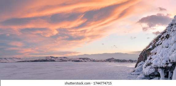 Red clouds at sunset over winter ice-covered Lake Baikal with icy rock on the right