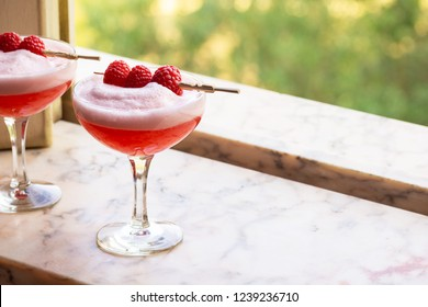 Red Clover Club Cocktails with Layered Egg White Foam and Raspberry Garnish in Marble Windowsill