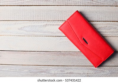 Red clutch purse lies on a flat wooden surface. Women's accessories. Fashionable style. Flat lay.