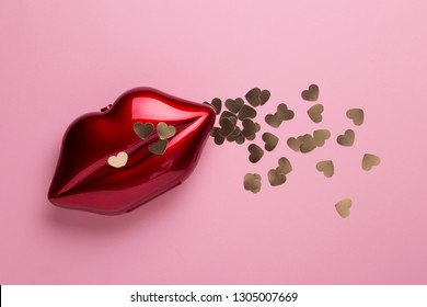 Red clutch shaped as female mouth, shiny red lips. Chic trendy fashion accessory, sensual kiss Valentines Day, gold glitter hearts