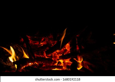 Red coals with fire on a black background. Burning coals and wood in the fire. Burning wood to keep warm and heat.