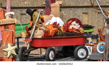 A red coaster wagon decorated for Thanksgiving. The 4-wheeled cart is filled with a pumpkin, autumn leaves, bramble and a holiday stuffed turkey doll. The red wagon is a classic, childhood toy.