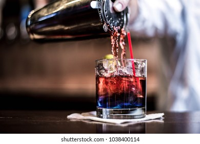 A red cocktail being poured from a shaker into a glass on a napkin on a bar top