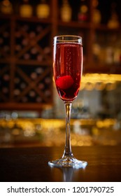 Red Cocktail in Champagne Glass near in the Bar with Amazing Blurred Background.