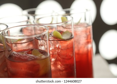 Red cocktail with lime rind wedge
