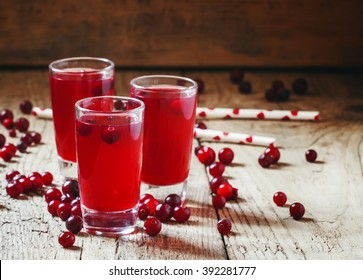 Red cocktail with natural cranberry juice and vodka, old wooden background, selective focus