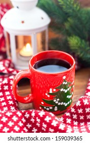 Red coffee cup with candle and spruce on the background