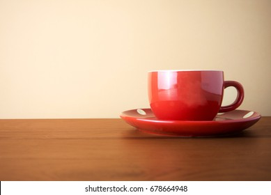 red coffee cup on wood table
