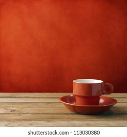 Red coffee cup on wooden deck tabletop against red grunge wall