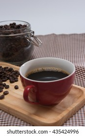 red coffee cup on wooden tray and coffee bean in jar on Plaid fabric