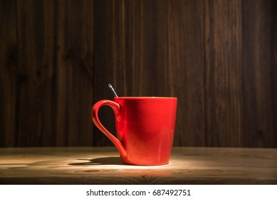 red coffee cup on wooden table background