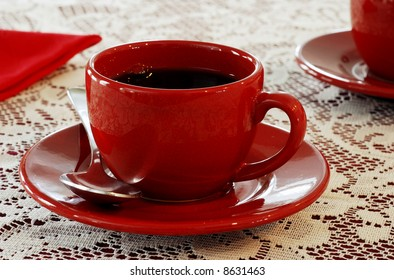 A red coffee cup and saucer on a white lace tablecloth with an out of focus red cup in the background.