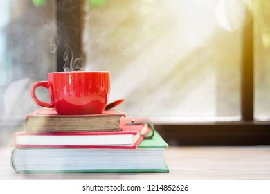 Red coffee cup with smoke on top of stacked old books on wood table with window light. Merry Christmas concept background. Resting, relaxing time or reading.