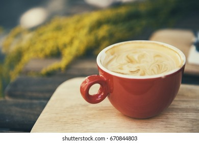 Red coffee cup in a summer day with flowers in background