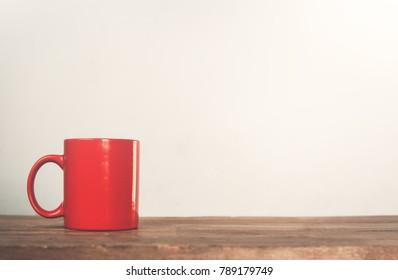 Red coffee mug on a wood.