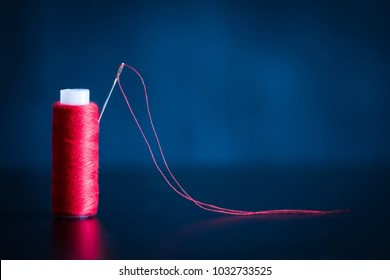 red coil of thread with needle on the dark background