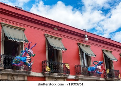 Red colonial building and artwork known as alebrije in Oaxaca, Mexico