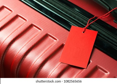 Red color empty travel luggage label on handle
