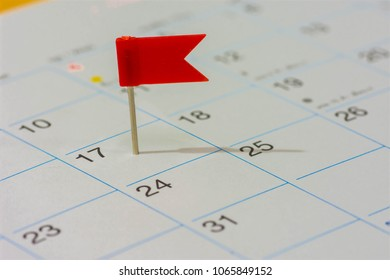 Red color flag pin on calendar in 17th of month. Red color flag pin thumbtack a date on calendar or planner. Tax Day falls on April 17th each year. (selective focus)