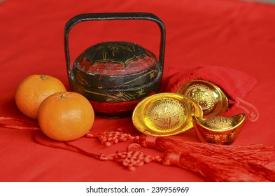 Red color, golden pineapples, mandarin oranges and gold ingots signifies prosperity / Auspicious ornaments / Chinese new year background